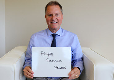 "Photo of Lee Osterberg holding sign that reads: ""People, service and values"""
