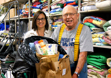 Photo of Lester Heggernes at Union Gospel Mission holding a basket of donated bath items.